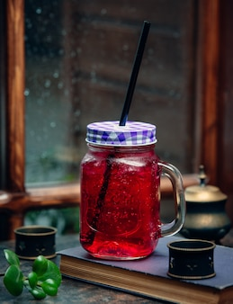 Iced pink drink in mason jar with black straw in front of the window