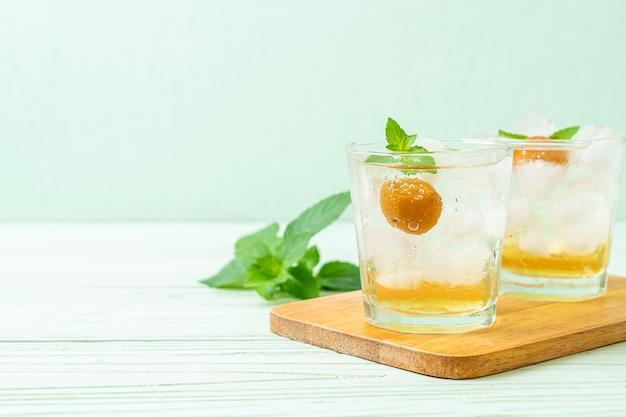 木製のテーブルにソーダとペパーミントを入れたアイスプラムジュース-リフレッシュドリンク