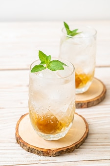 Замороженный сливовый сок с содой и мятой на деревянном столе - освежающий напиток
