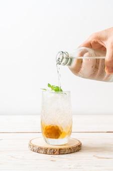 木製のテーブルにソーダとペパーミントを添えたアイスプラムジュース-リフレッシュドリンク
