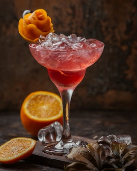 Iced red cocktail with orange flower