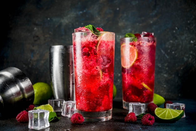 Iced summer drink cocktail, raspberry and lime lemonade with fresh mint and lime, dark blue rusty background