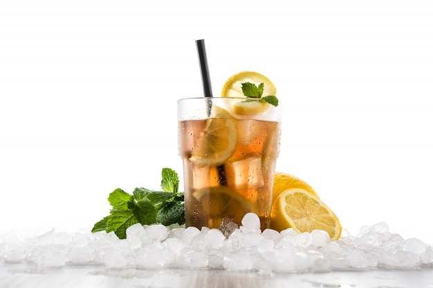 Iced tea drink with lemon in glass and ice on white wooden table