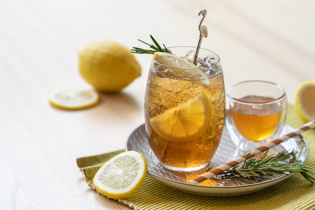 Iced tea with lemon and honey on plate, refreshing summer drink.