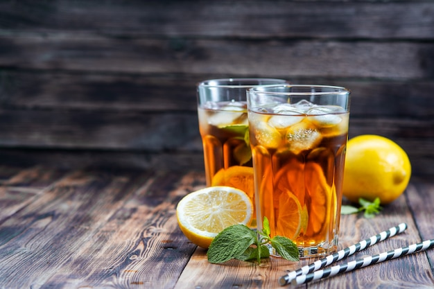 Iced tea with lemon and ice on a wooden table