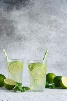 Холодный чай с лаймом. холодный лимонад с лаймом на бетонном фоне.
