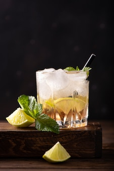 Iced tea with mint, lime slices and strawberry syrup