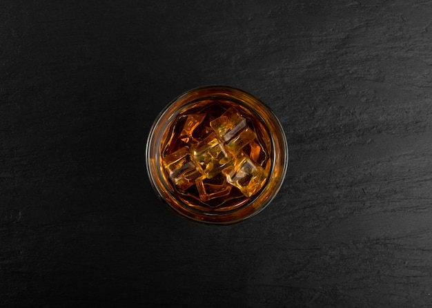 Iced whiskey glass on natural black stone background
