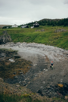 Scenario islandese della spiaggia, l'uomo cammina in maglione