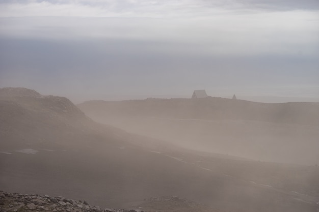 Исландская хижина на вулканическом ландшафте во время сильной пепельной бури на пешеходной тропе фиммвордухальс ...