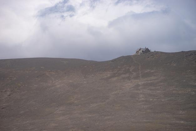 Исландская хижина на вулканическом ландшафте во время сильной пепельной бури на пешеходной тропе фиммвордухальс. исландия.
