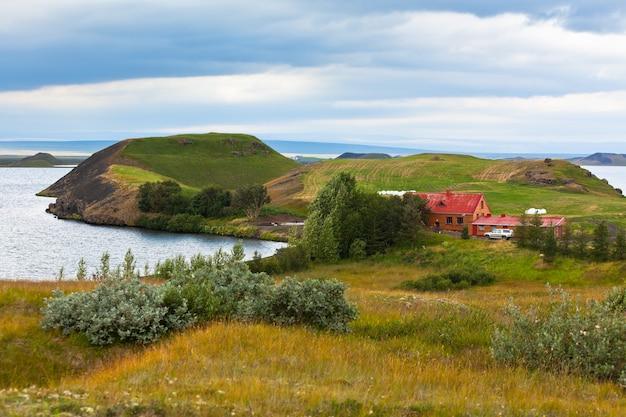 ミーバトン湖の海岸線にコテージがあるアイスランドの風景。横ショット