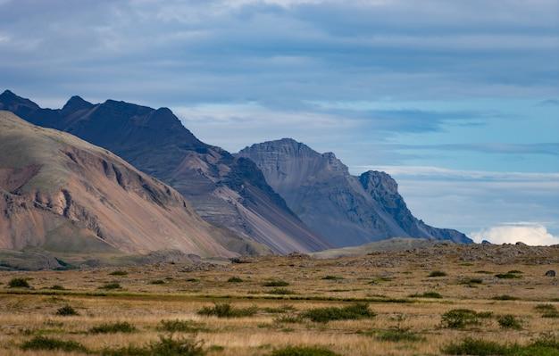 Исландский пейзаж с горами, голубым небом и зеленой травой на переднем плане. часть западного фьорда. Premium Фотографии