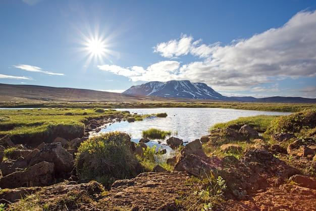 Исландский летний пейзаж природы с солнцем, озером и горой.