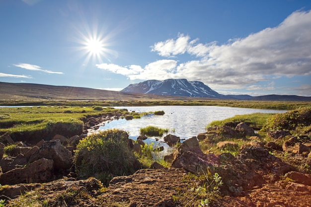 Icelandic summer nature scenery with sun, lake and mountain.