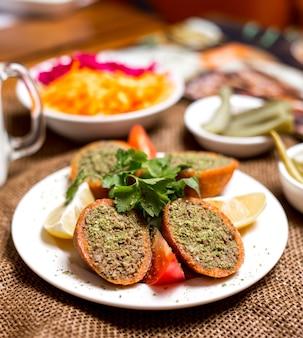 Турецкие фаршированные фрикадельки ichli kofte с лимоном, помидорами и петрушкой