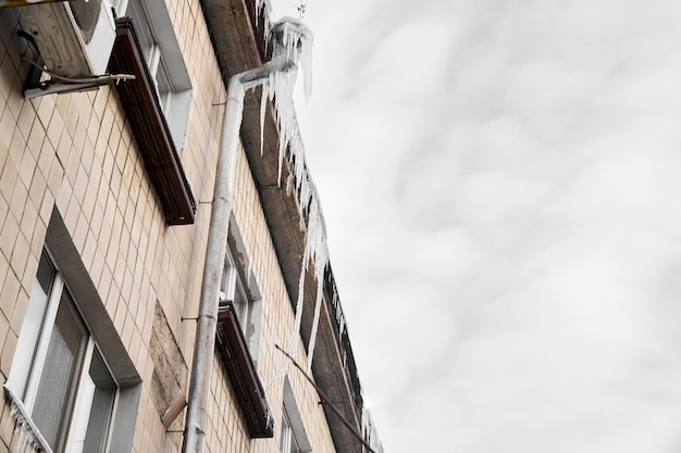 Сосулька на крыше трубы, здание покрыто большими сосульками