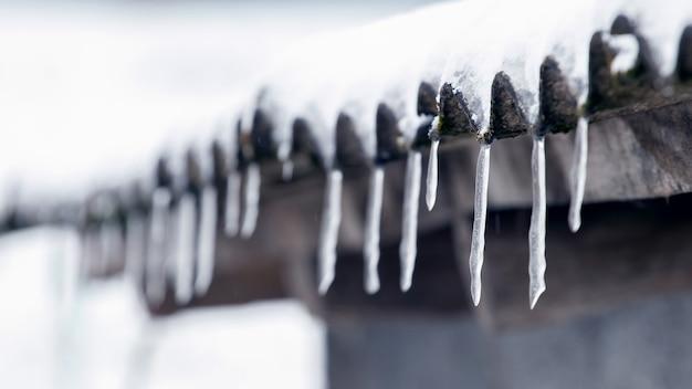 雪解け後、つららは家の屋根からぶら下がっています