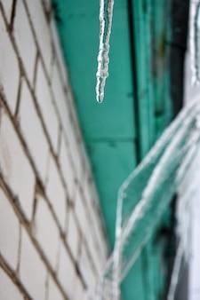 집 지붕에 고드름이 매달려 있습니다.