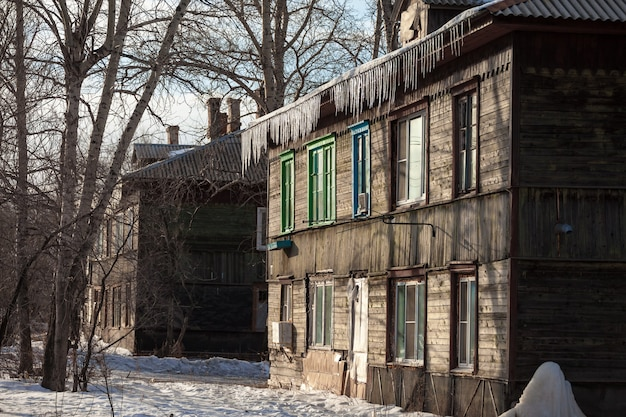 Сосульки свисают с крыши старого дома