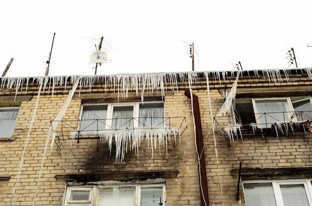 Сосульки свисают с крыши многоэтажного дома