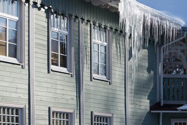 Сосульки свисают с крыши деревянного здания зимой в солнечную погоду