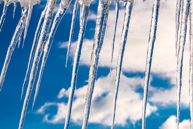Сосульки, свисающие с крыши в солнечный зимний день