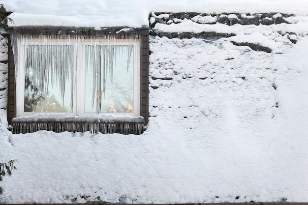 Сосульки на окне дома в морозный день.