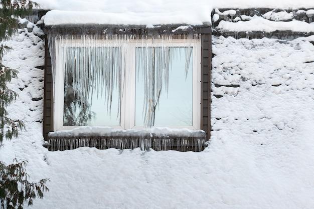 Сосульки на окне дома в морозный день ..