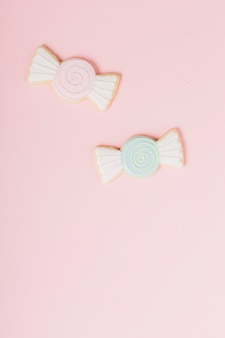Icing cookies in chocolate shape against pink backdrop