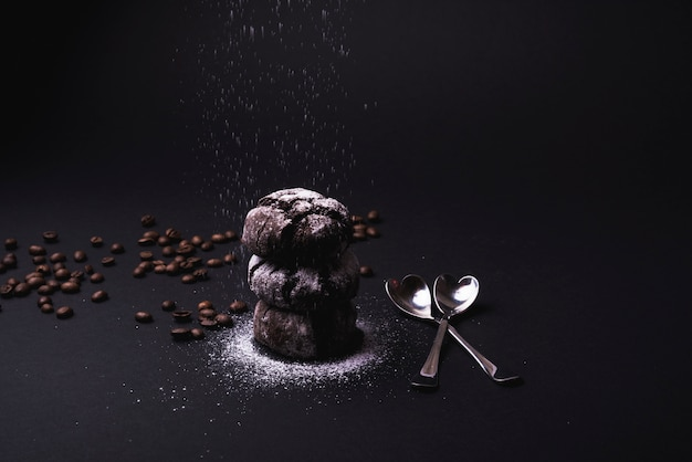 Icing sugar falling on cocoa cookies stacked with roasted coffee beans and spoon on black backdrop
