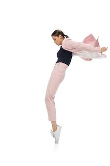 アイコン。カジュアルな服やスーツを着て踊り、文化の歴史から伝説的な動きや有名人の踊りを作り直す幸せな若い女性。白で隔離。アクション、モーション、名声のコンセプト。創造的な職業。
