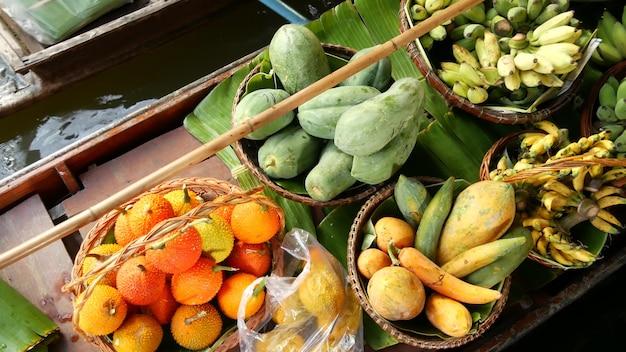 Знаменитый плавучий рынок лат майом в азии. канал реки клонг, длиннохвостая лодка с тропическими экзотическими красочными фруктами