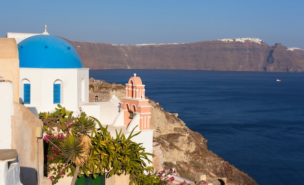 Iconic church with blue cupola and pink bell tower in oia, santorini.