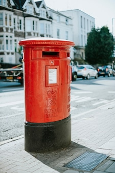 Iconic red British mailbox in a city
