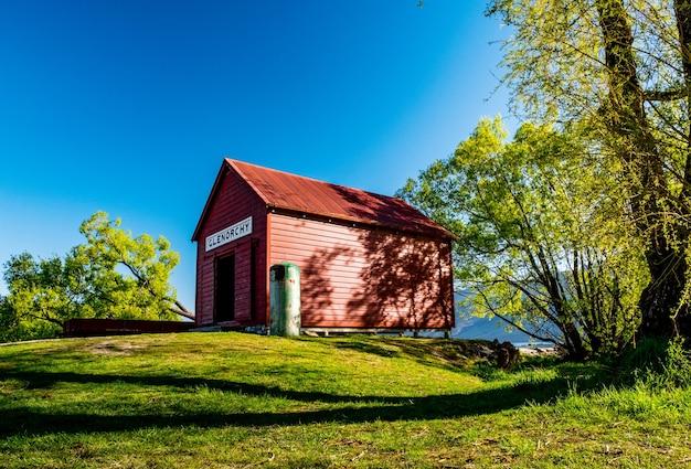 「ニュージーランド、グレノーキーの湖のほとりにある象徴的な赤い建物と美しい風景。