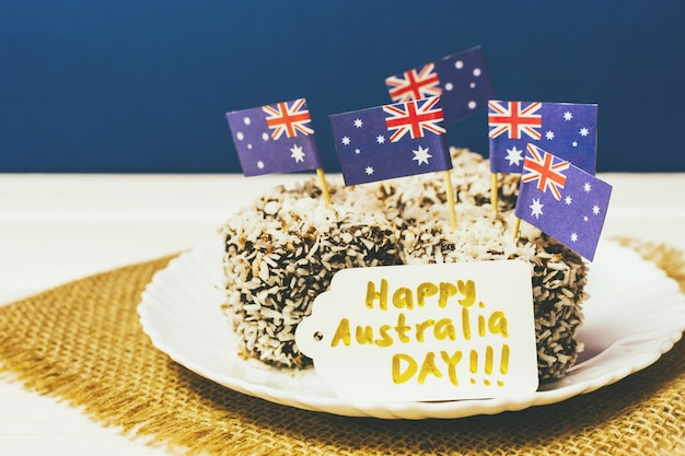 Iconic traditional australian party food, lamington cakes on a red, white and blue background. australia flag.