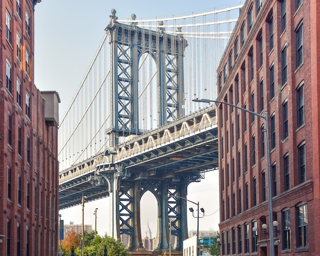 Iconic view of manhattan bridge from washington street. red brick street buildings leading to the bridge at dusk. brooklyn. nyc, usa.