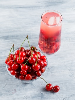 Icy cherry drink in a jug with cherries high