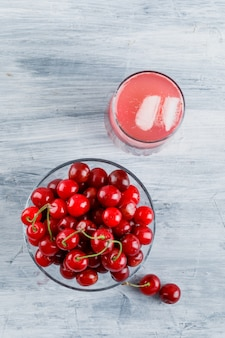 Icy cherry drink in a jug with cherries