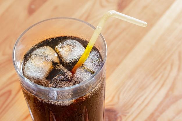 Ледяной холодный напиток в стакане, вид сверху. стакан прохладного газированного напитка со льдом на деревянный стол
