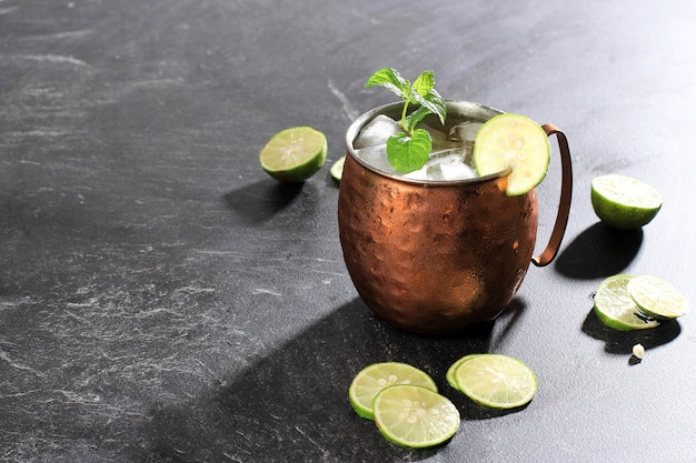 Icy cold moscow mule coctail on copper mug  with ginger beer, lime,  and vodka, garnish with mint leaf. isolated on  black slate background