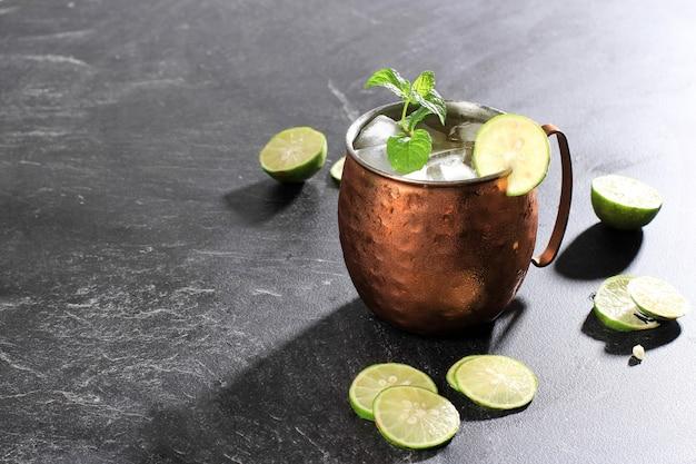 Ледяной коктейль «московский мул» на медной кружке с имбирным пивом, лаймом и водкой, украшенный листом мяты. изолированные на фоне черного сланца