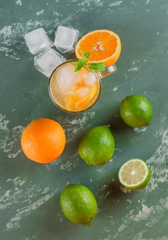 Icy detox water in a cup with oranges, mint, limes flat lay on a plaster surface