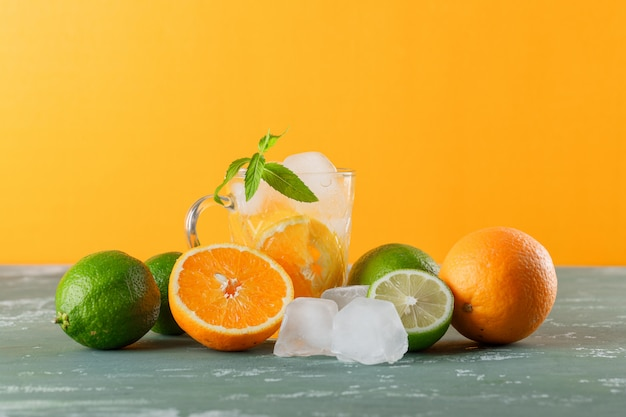Icy detox water in a cup with oranges, mint, limes side view on plaster and yellow background