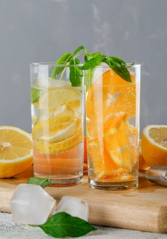 Icy detox water in glass with orange, lemon, mint, cutting board close-up on grunge and grey wall
