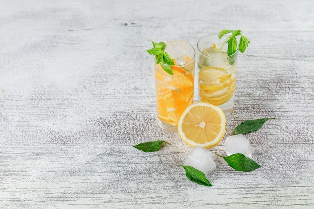 Icy detox water in glass with orange, lemon, mint high angle view on a grunge background