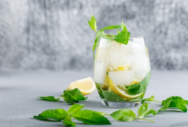 Icy detox water with lemon and mint in a glass on grey and grunge surface