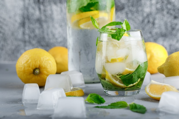 Icy detox water with lemons, mint in glass and bottle on grey and grungy surface