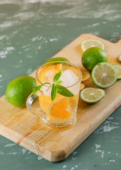 Icy detox water with orange, limes, mint, cutting board in a cup on plaster , high angle view.